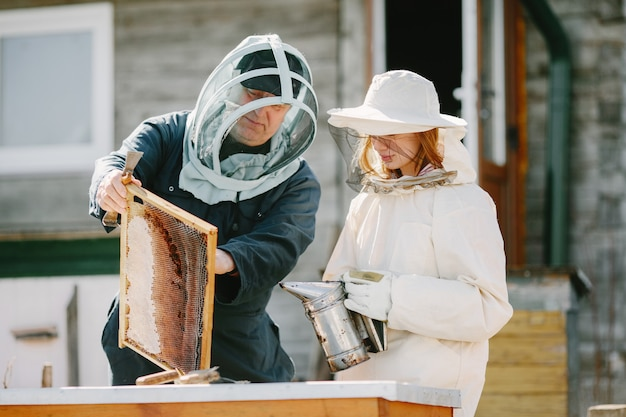 Dos apicultores trabajando en colmenar. trabajando en equipo de overol.