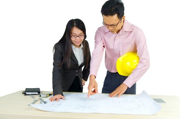Dos arquitectos discutiendo nuevo proyecto en oficina. mirando el plano.