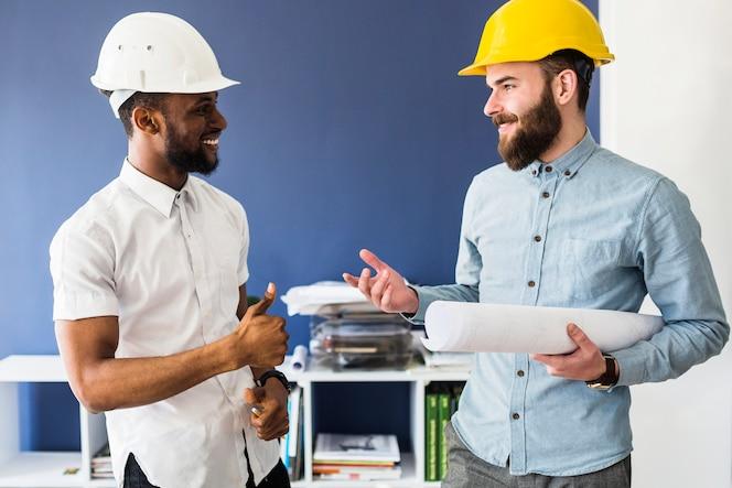 Dos arquitectos hombres exitosos conversan en la oficina
