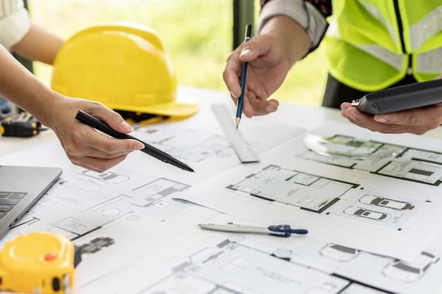 Dos arquitectos-ingenieros están consultando para modificar los planos de la casa contratada, tienen una reunión para inspeccionar los diseños de la casa antes de reunirse con el cliente. ideas de diseño para el hogar.