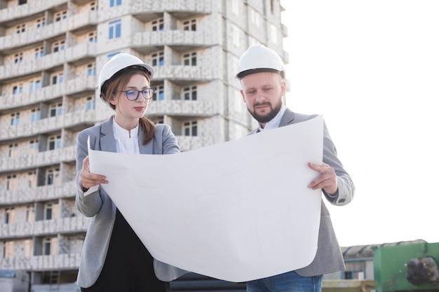 Dos arquitectos profesionales con planos y mirándolo cerca de la obra