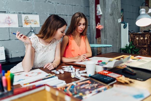 Dos artistas femeninas dibujando elementos decorativos sentado en el escritorio en estudio creativo