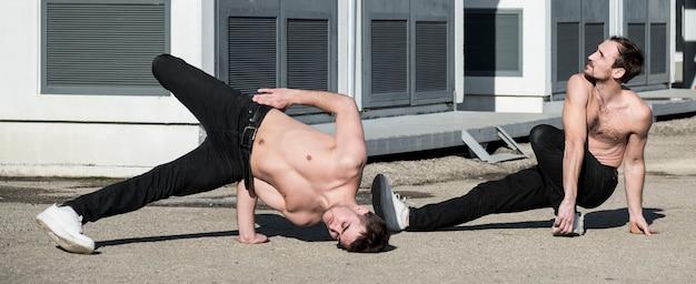 Dos artistas de hip hop sin camisa que practican la rutina de baile afuera