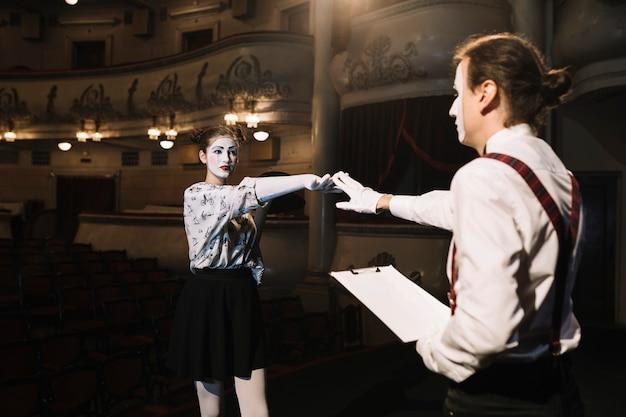 Dos artistas de mimo masculinos y femeninos ensayando en el escenario en el auditorio