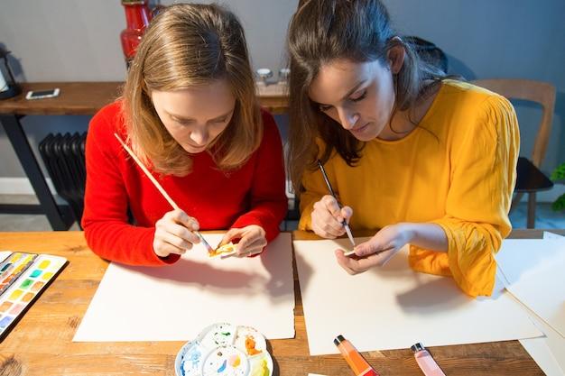 Dos artistas serios trabajando con pincel y paleta.