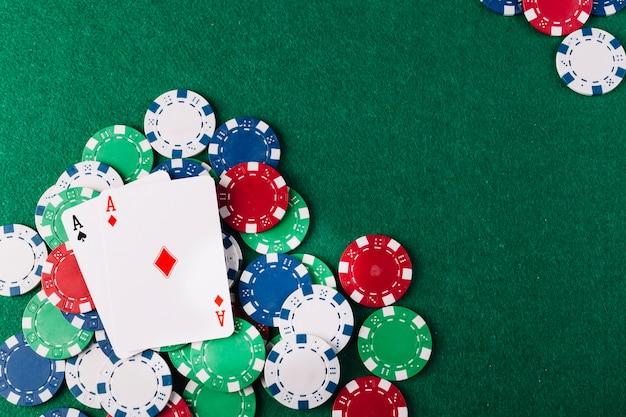 Dos ases jugando a las cartas y fichas en la mesa de poker verde