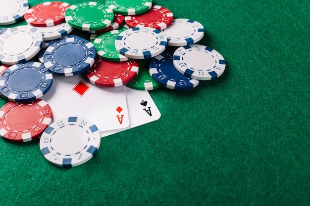Dos ases jugando a las cartas y fichas sobre fondo verde