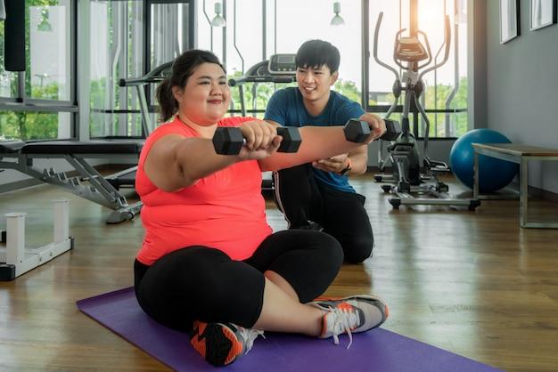Dos asiático entrenador hombre y mujer con sobrepeso haciendo ejercicio con pesas juntos en el moderno gimnasio, feliz y sonríe durante el entrenamiento. las mujeres gordas cuidan la salud y quieren perder el concepto de peso.