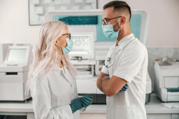 Dos asistentes de laboratorio dedicados de pie en el laboratorio y hablando sobre una nueva cura para el coronavirus.