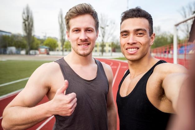 Dos atleta masculino sonriente en la pista de carreras tomando selfie en teléfono móvil