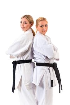 Dos atletas de chicas con cabello rubio en kimono con cinturones negros posando en el stand de karate
