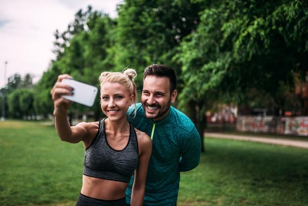 Dos atletas haciendo selfie en el parque.