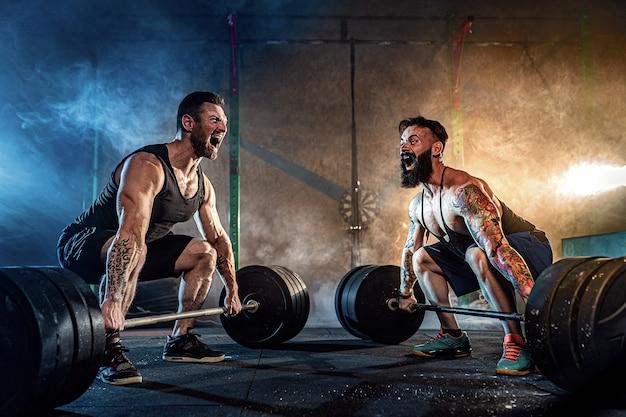 Dos atletas tatuados con barba muscular que entrenan en el gimnasio