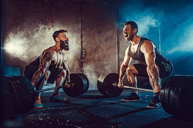 Dos atletas tatuados barbudos musculosos entrenando, levantando la barra de peso pesado en humo en el gimnasio