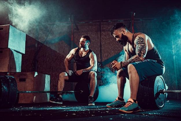Dos atletas tatuados barbudos musculosos se relajan después del entrenamiento, levantando peso pesado