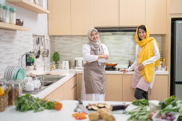 Dos atractiva joven musulmana preparando la cena iftar juntos. ramadán y eid mubarak cocinando en la cocina.