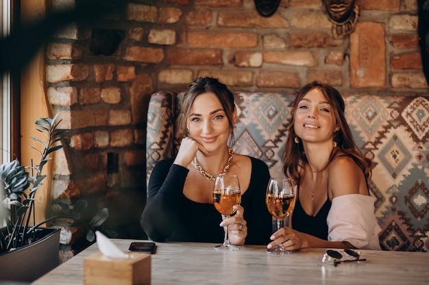 Dos atractivas chicas sentadas en un café y bebiendo vino