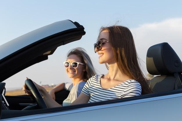Dos atractivas mujeres jóvenes en un coche descapotable