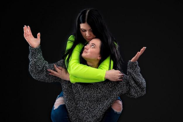 Dos atractivas mujeres jóvenes divirtiéndose, uno lleva al otro en la espalda y se ríe, aislado en la oscuridad
