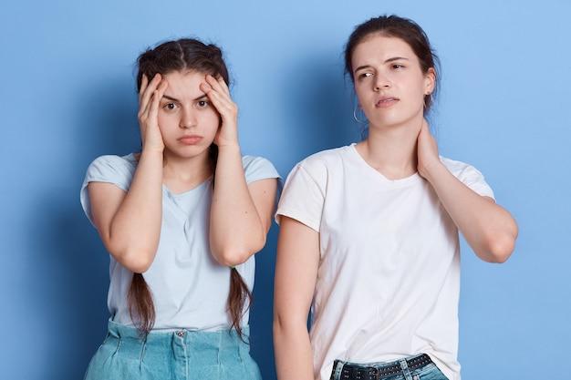 Dos atractivas mujeres jóvenes de pelo oscuro pensando