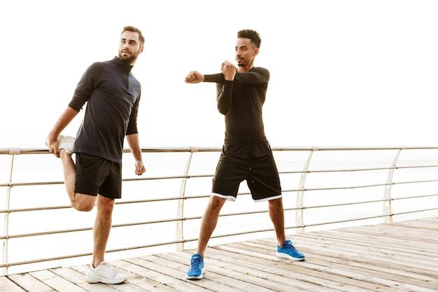 Dos atractivos deportistas sanos jóvenes sonrientes al aire libre en la playa, entrenar juntos, haciendo ejercicios de estiramiento