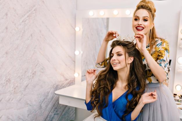 Dos atractivos modelos alegres con aspecto elegante divirtiéndose en el salón de belleza