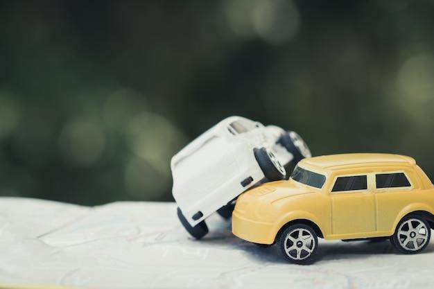 Dos autos en miniatura choque en carretera, juguetes rotos, auto auto en mapa de la ciudad