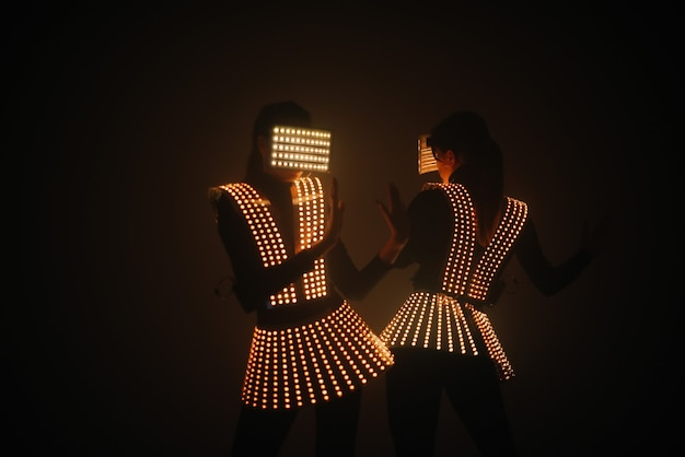 Dos bailarinas de discoteca sexy se mueven con disfraces uv. fiestas y bailes.