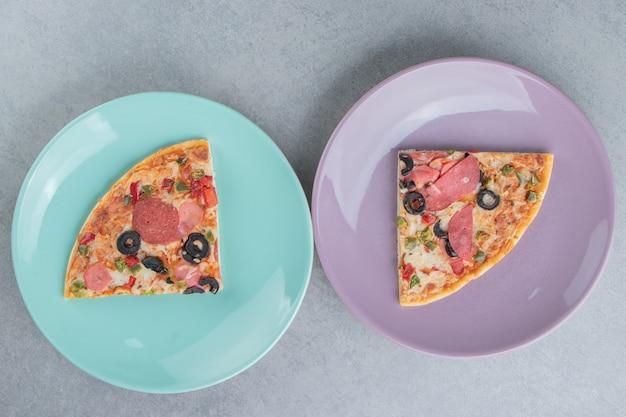 Dos bandejas con porciones de pizza en mármol