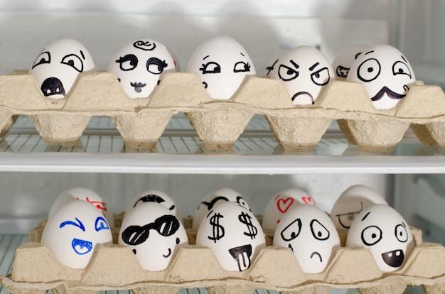 Dos bandejas con sonrisas pintadas en los huevos en los estantes del refrigerador, de cerca