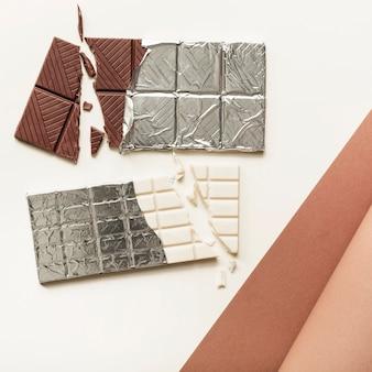 Dos barras de chocolate en lámina de plata sobre fondo blanco.
