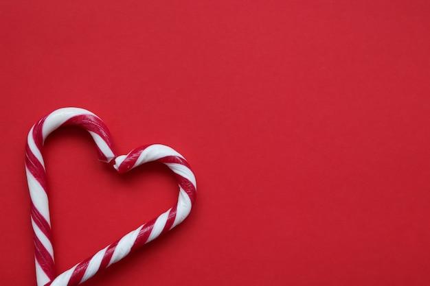 Dos bastones de caramelo de navidad formando una forma de corazón sobre fondo rojo.