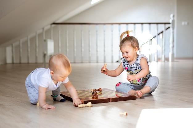 Dos bebés niño y niña jugando al ajedrez en el piso de madera blanca en casa.