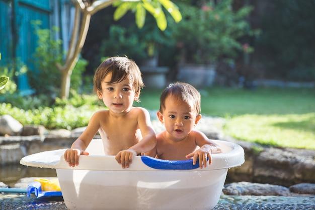 Dos bebés tomando un baño juntos