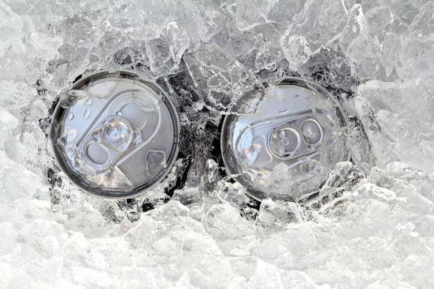 Dos bebidas en lata heladas sumergidas en hielo helado.