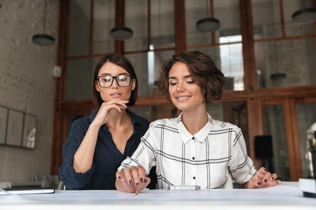 Dos bellas mujeres muy sonrientes sentados a la mesa