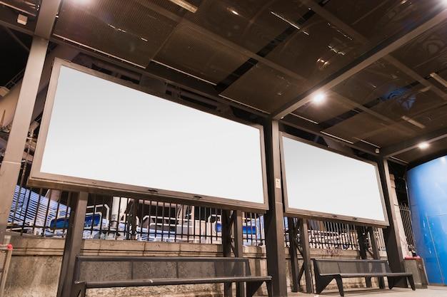 Dos en blanco anuncio publicitario blanco en la parada de autobús iluminada