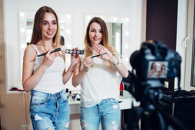 Dos bloggers de belleza filmando una guía de compras de maquillaje que muestra sombras de ojos y pinceles contra espejos de maquillaje en el estudio