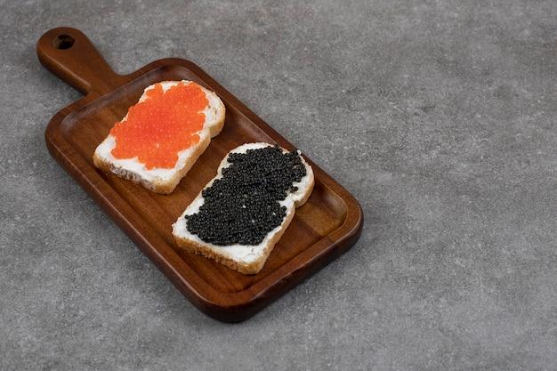 Dos bocadillos frescos caviar rojo y negro sobre tabla de cortar de madera.