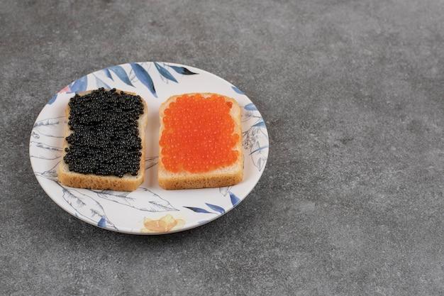 Dos bocadillos frescos con caviar rojo y negro.