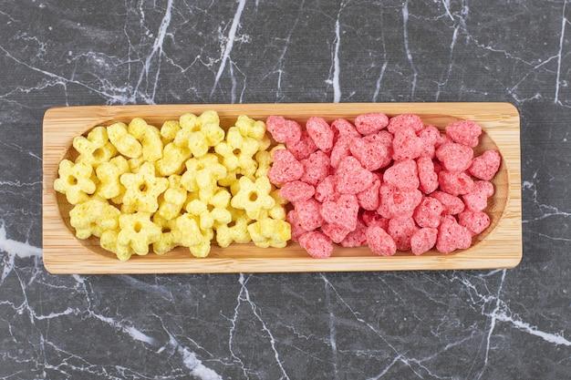 Dos bolas de cereales de colores sobre placa de madera.