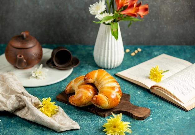 Dos bollos con forma de croissant colocados en una tabla de madera