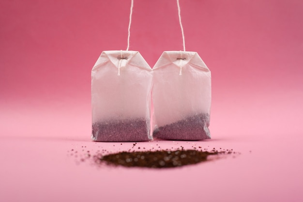 Dos bolsas de papel con té y con un montón de té negro suelto en un primer plano de fondo rosa.