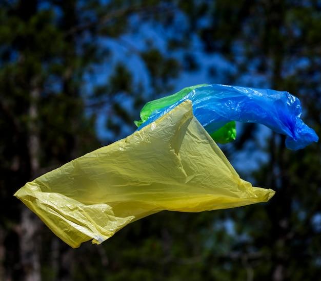 Dos bolsas de polietileno para basura vuelan en el aire contra un bosque de pinos.