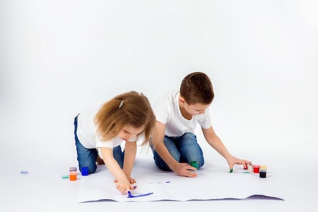 Dos bonitas amigas niño y niña dibujan con pinturas