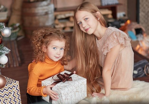 Dos bonitas hermanas sentadas en el suelo en la víspera de navidad.
