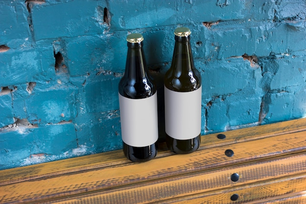 Dos botellas de cerveza con etiquetas en blanco se colocan en un soporte de madera en el fondo de una pared de ladrillo