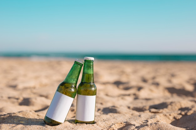 Dos botellas de cerveza en la playa de arena
