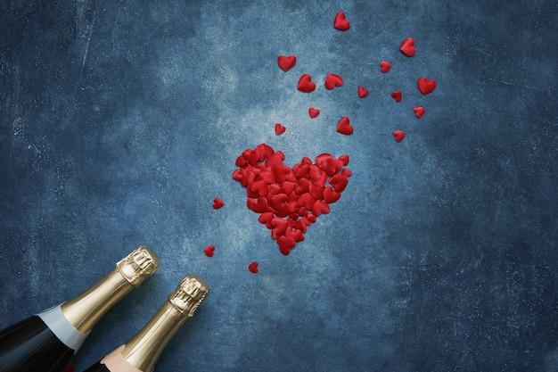 Dos botellas de champán con corazones rojos sobre fondo azul.