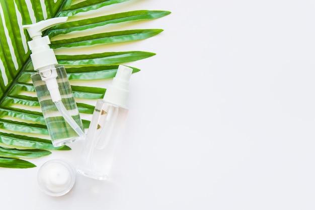 Dos botellas cosméticas transparentes con rociador y crema hidratante en una hoja verde sobre fondo blanco.